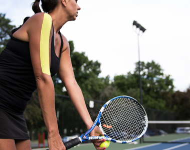 female tennis player with yellow kinesiology tape on upper arm