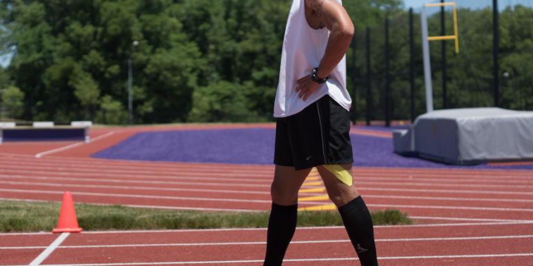 male track athlete wearing yellow kinesiology tape on thigh