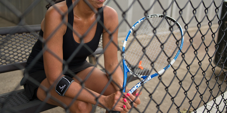 female tennis player taking a break on a bench