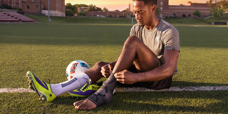 male soccer player putting on OmniForce Ankle Support