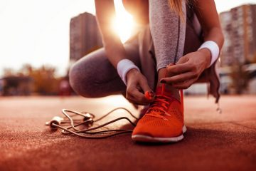 person tying their shoe before running