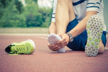 jogger holding foot in pain