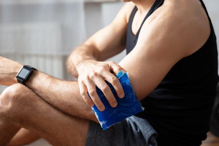 man applying heat to an injured elbow