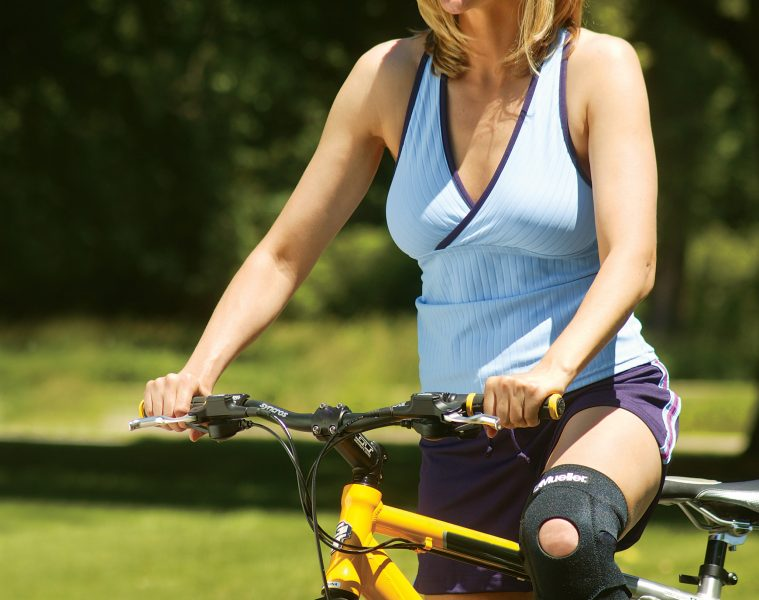 woman wearing a Mueller knee brace while riding a bike