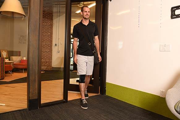 man walking into work office with knee brace on