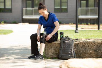 woman in medical field wearing a Mueller knee brace
