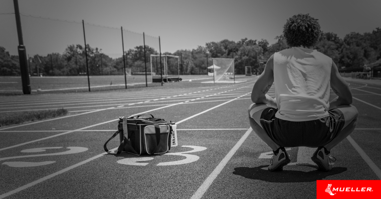 athlete squatting down next to a Mueller Athletic Training Kit