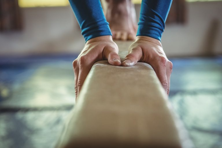 close-up of gymnast's hands on the balance beam