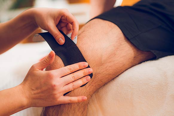 kinesiology tape being applied to a man's knee