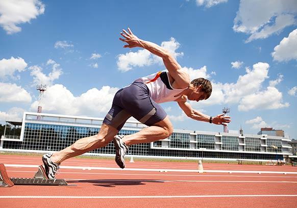 track runner leaving starting line