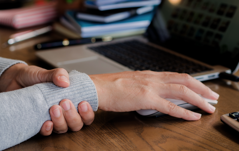 hand with Carpal Tunnel Syndrome resting on laptop