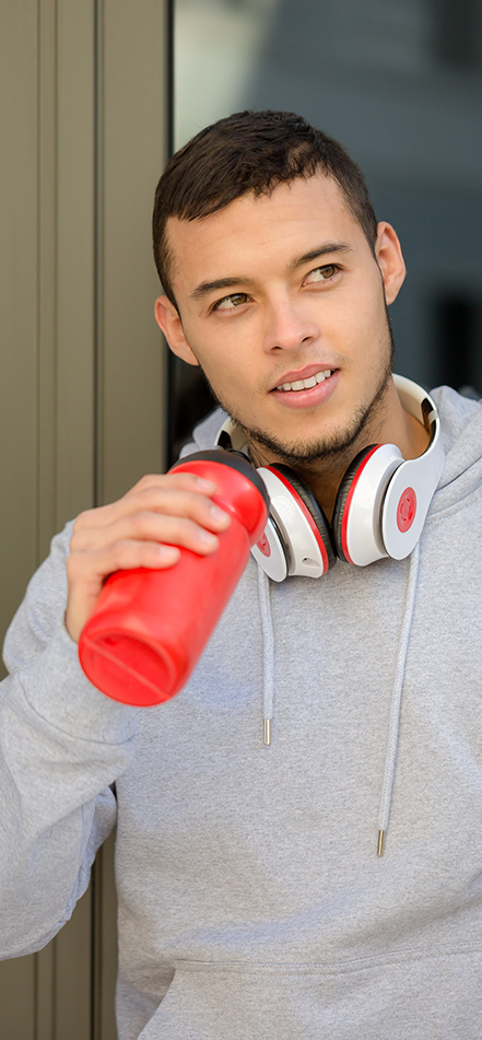 man drinking from a red water bottle
