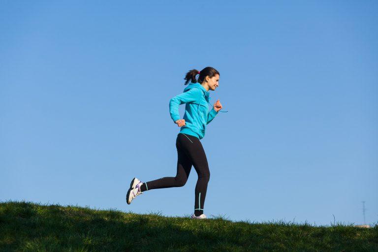 female runner against a cloudless blue sky