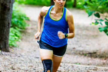 woman wearing a Mueller knee brace while running on a trail through the woods
