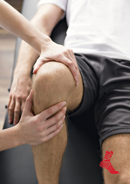 athletic trainer examining a knee injury
