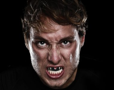 male athlete showing his fang mouthguard