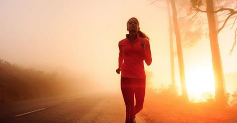 woman running with the sunset behind her