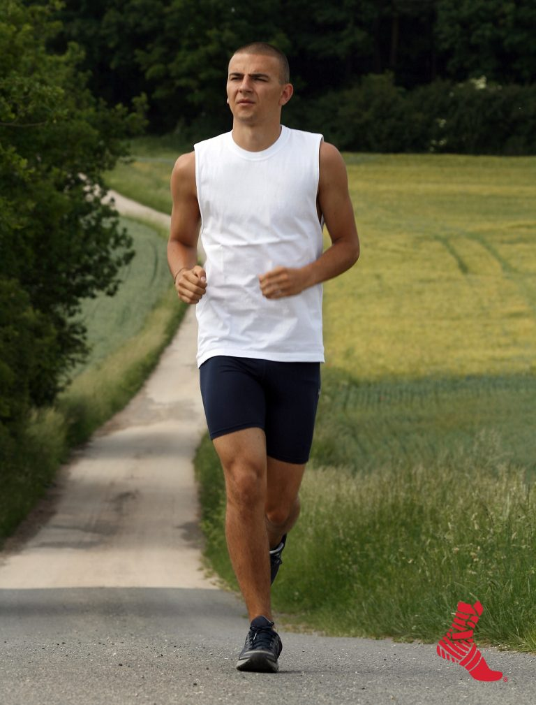man running on path wearing compression shorts