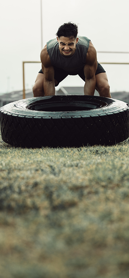 man lifting tire for exercise