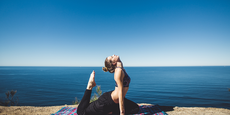 woman doing yoga near the water