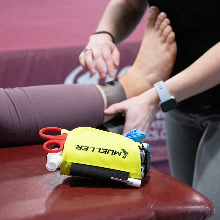 athletic trainer examining an ankle injury