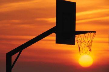 outline of basketball hoop against an orange sunset