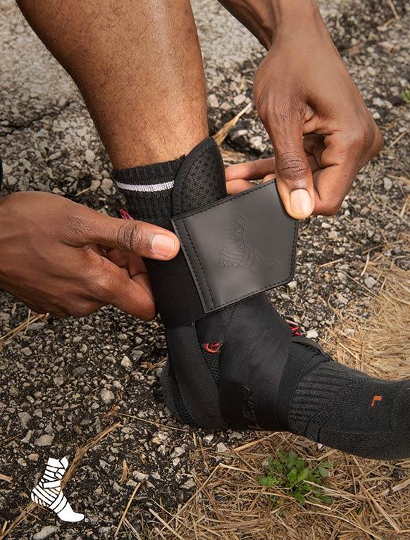 man adjusting black Mueller ankle brace