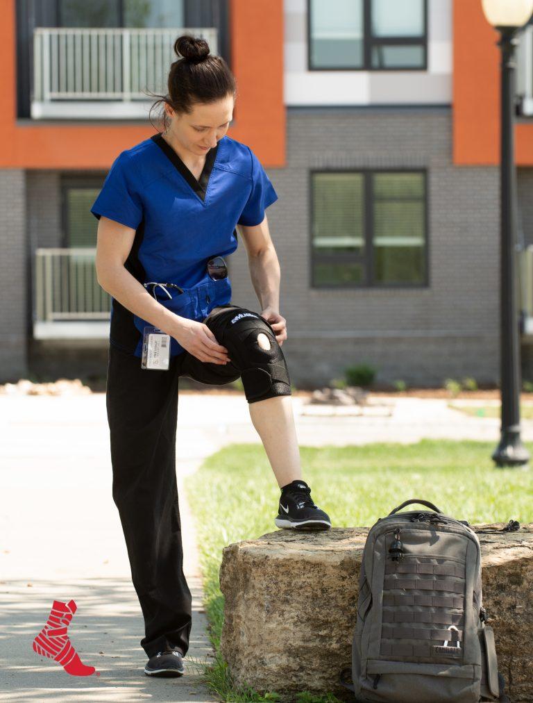 medical professional wearing a Mueller knee brace under her scrubs