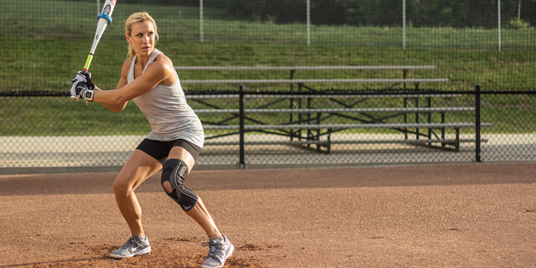 woman wearing a Mueller knee brace while playing recreational softball