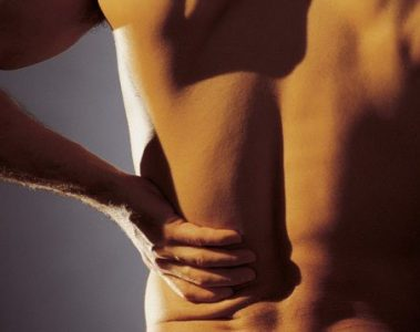 man holding his lower back in pain