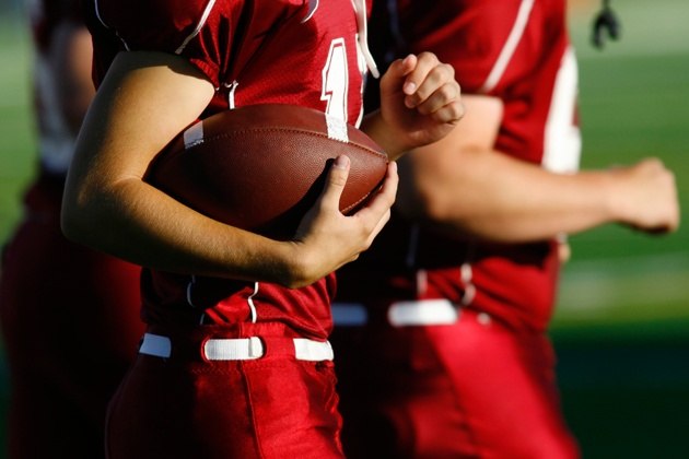 young football player cradling football while jogging